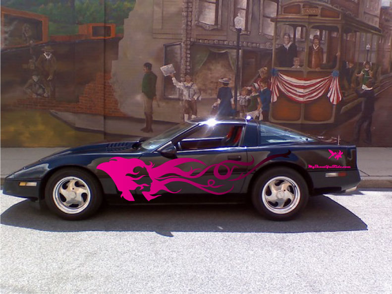 Sexy Black Corvette with hot pink fade decal of woman's face by a historic mural