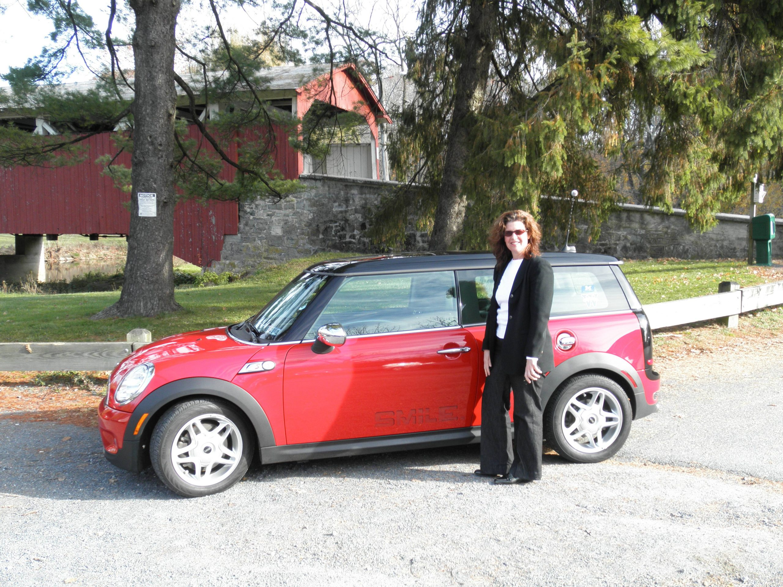 Red Mini Cooper with subtle smile decal by covered bridge in Pennsylvania