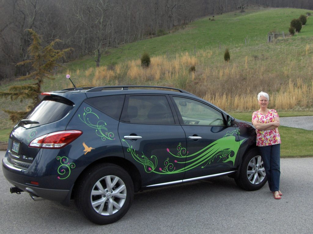 Woman standing in front of Black Murano with green decals